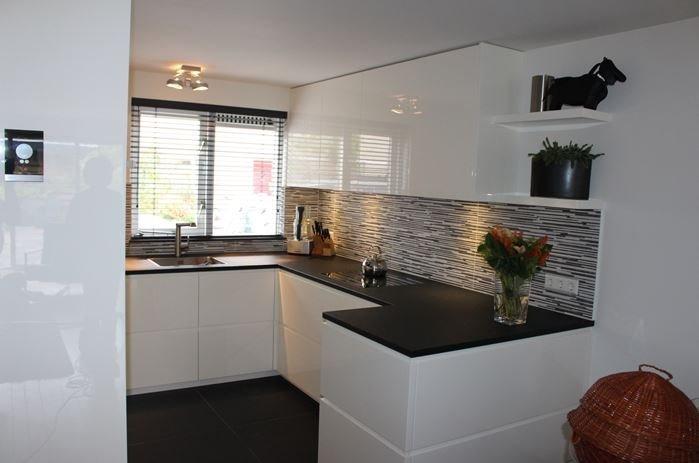 Keuken met hoogglans wit gespoten MDF fronten en door lopend greep in het gehele front.